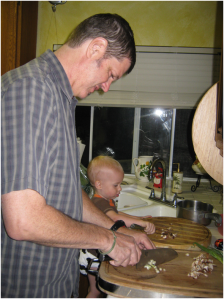 Photo of JM Bray Teaching his 2 year old grandson some kitchen skills
